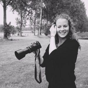 Kim lachend met haar camera in haar hand. Zwart wit foto.