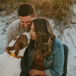 man en vrouw knuffelen met een hond op de duinen